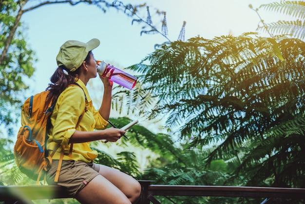 Młoda kobieta podróżuje nagrywając i badając naturę lasu.