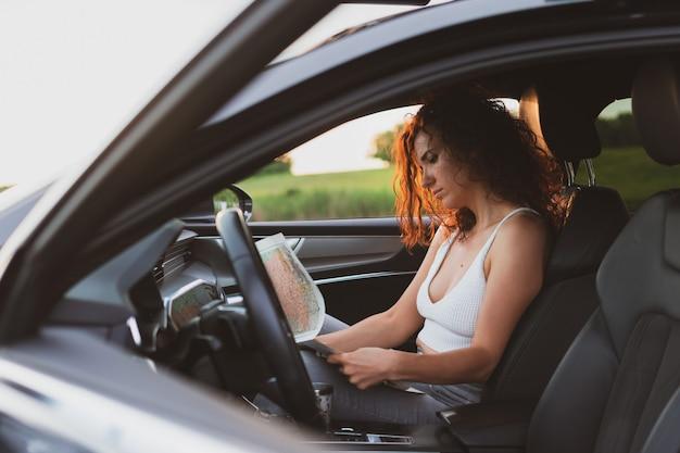 Młoda kobieta podróżuje po drogach samochodem, spójrz na mapę koncepcja wakacji