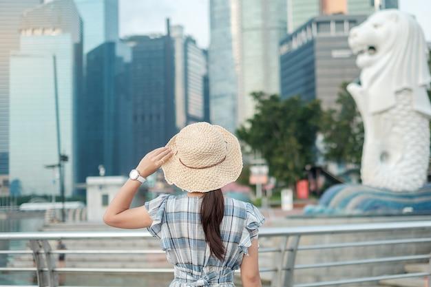 Młoda kobieta podróżuje z kapeluszem w ranku, szczęśliwa azjatycka podróżnik wizyta w singapur miasta śródmieściu. punkt orientacyjny i popularny wśród atrakcji turystycznych. asia travel concept