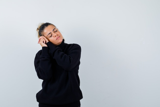 Młoda kobieta poduszka twarz na splecionych dłoniach w czarnym swetrze z golfem i patrząc śpiący. przedni widok.