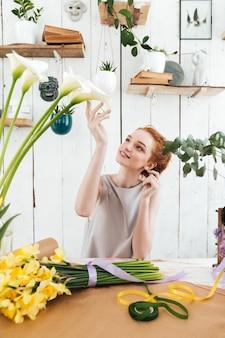 Młoda kobieta podziwia piękne kwiaty w warsztacie
