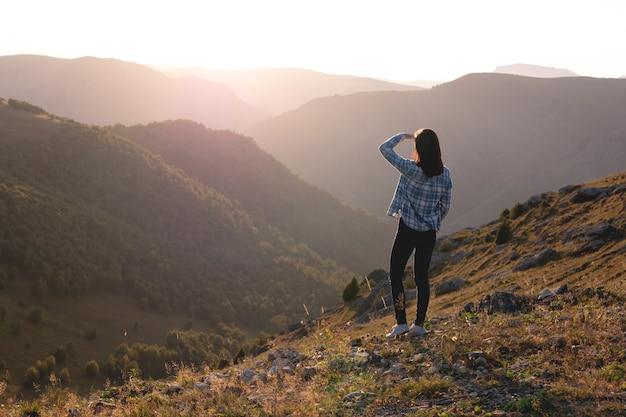Młoda kobieta podziwiając zachód słońca w górach turysta na szczycie góry o zachodzie słońca promienie słońca