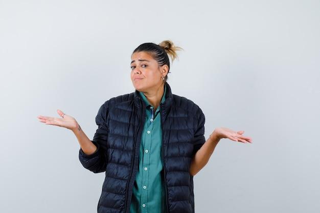 Młoda kobieta pokazując bezradny gest w koszuli, pikowanej kurtce i patrząc zdezorientowany. przedni widok.