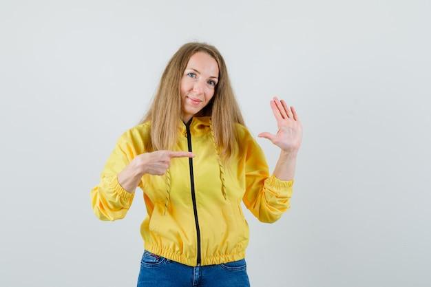 Młoda kobieta pokazując gest stopu i wskazując na niego w żółtej bomberce i niebieskim dżinsie i patrząc optymistycznie, widok z przodu.