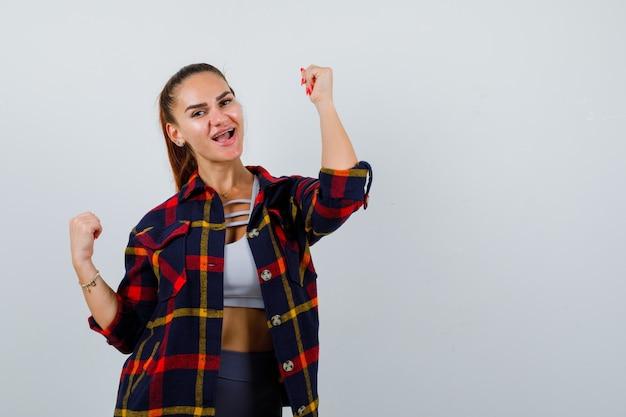 Młoda kobieta pokazując gest zwycięzcy w crop top, kraciaste koszule i patrząc błogo. przedni widok.