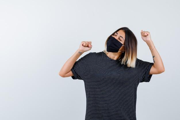Młoda kobieta pokazując gest zwycięzcy w czarnej sukience, czarnej masce i patrząc na szczęście, widok z przodu.