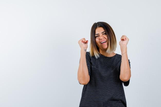 Młoda kobieta pokazując gest zwycięzcy w czarnej sukni i patrząc na szczęście. przedni widok.
