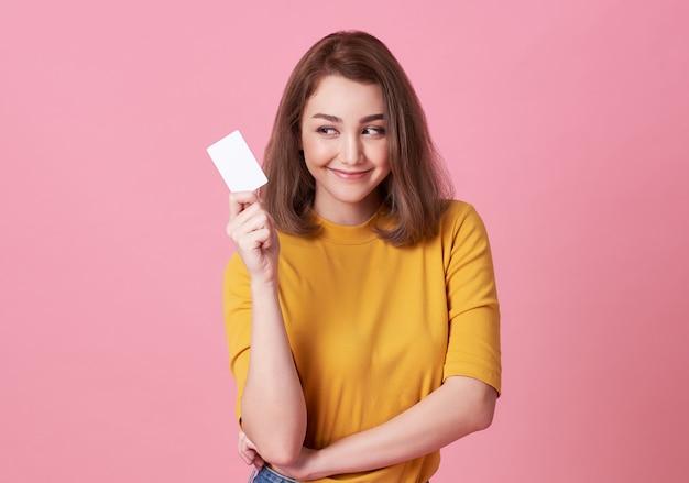 Młoda kobieta pokazując kartę kredytową i patrząc odizolowane na różowo