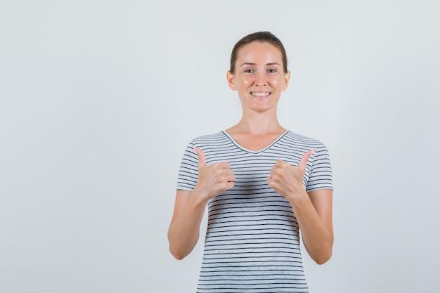 Młoda kobieta pokazując kciuki w pasiastej koszulce i patrząc wesoły, widok z przodu.