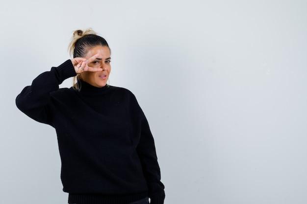 Młoda kobieta pokazując znak zwycięstwa w czarnym swetrze z golfem i patrząc błogi, widok z przodu.