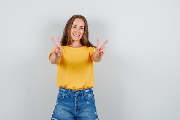 Młoda kobieta pokazując znak zwycięstwa w t-shirt, spodenki i wesoły wyglądający. przedni widok.