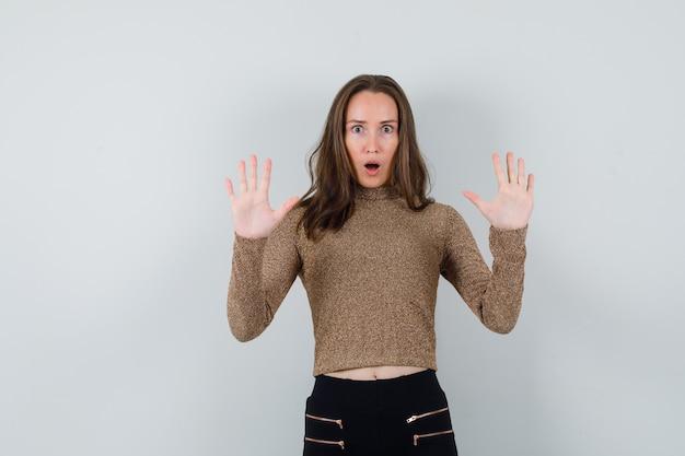 Młoda kobieta pokazująca gest kapitulacji w złoconym swetrze i czarnych spodniach i wyglądająca na zaskoczoną