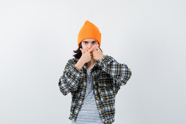 Młoda kobieta pokazująca gest przegranego w pomarańczowym kapeluszu wygląda poważnie