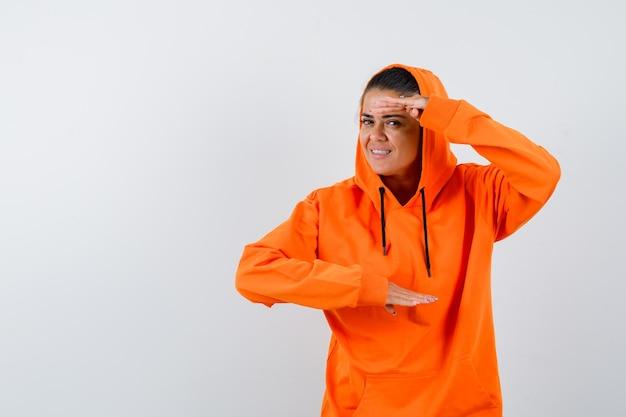 Młoda kobieta pokazująca łuski w pomarańczowej bluzie z kapturem i wyglądająca pięknie
