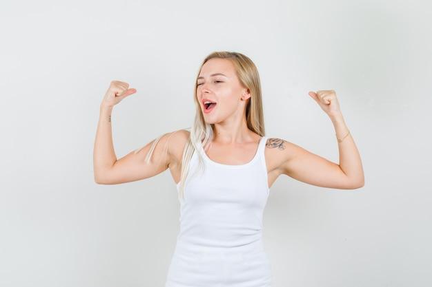 Młoda kobieta pokazująca mięśnie z mrugniętymi oczami w białym podkoszulku i wyglądająca energicznie