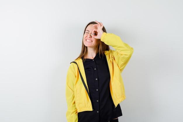 Młoda kobieta pokazująca ok znak na oku