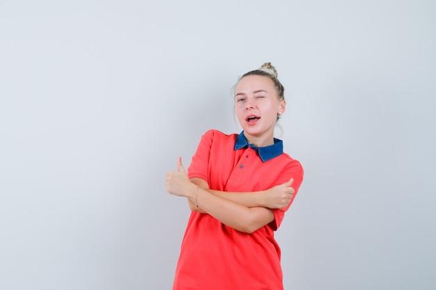 Młoda kobieta pokazująca podwójne kciuki do góry, mrugające okiem w koszulce i rozbrykana