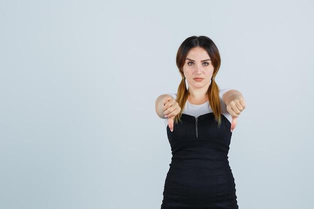Młoda kobieta pokazująca podwójne kciuki w dół i wyglądająca na niezadowoloną