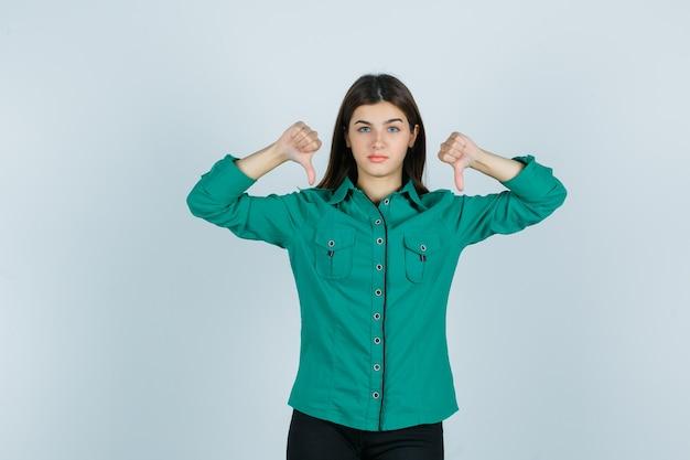 Młoda kobieta pokazująca podwójne kciuki w dół w zielonej koszuli i niezadowolona, widok z przodu.