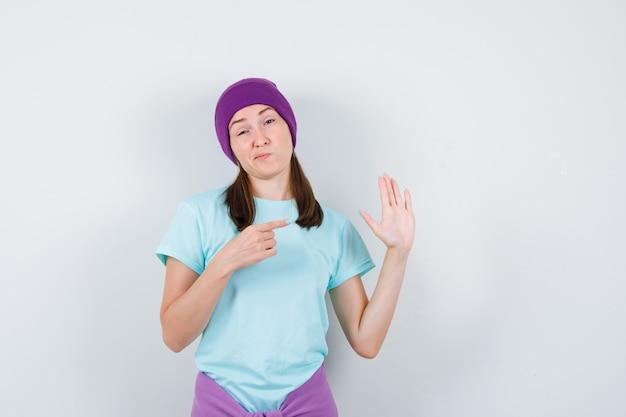 Młoda kobieta pokazująca znak stop, wskazująca palcem wskazującym, wykrzywione usta w niebieskiej koszulce, fioletowa czapka i wyglądająca na niezadowoloną, widok z przodu.