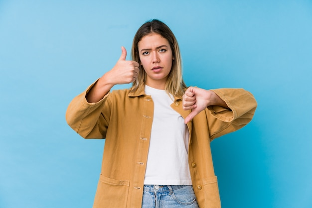 Młoda kobieta pokazuje aprobaty i kciuki zestrzela