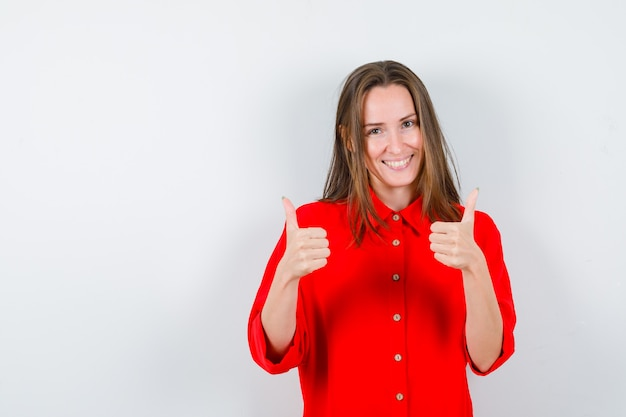 Młoda kobieta pokazuje aprobaty w czerwonej bluzce i wygląda na szczęśliwego, widok z przodu.
