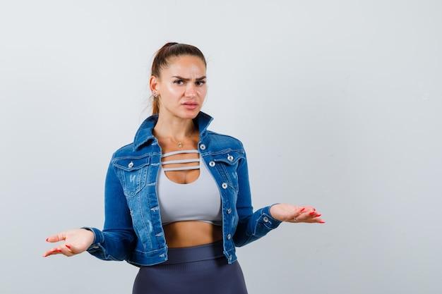 Młoda kobieta pokazuje bezradny gest w bluzce, kurtce, spodniach i patrząc poważnie. przedni widok.
