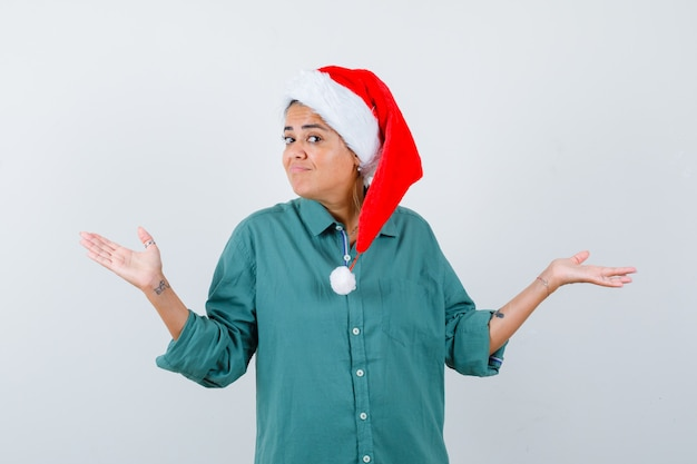 Młoda kobieta pokazuje bezradny gest w koszuli, kapeluszu santa i patrząc niezdecydowany, widok z przodu.