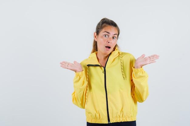 Młoda kobieta pokazuje bezradny gest w żółtym płaszczu przeciwdeszczowym i wygląda na zakłopotaną