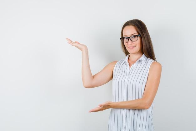 Młoda kobieta pokazuje coś lub wita w t-shirt i wygląda wesoło, widok z przodu.