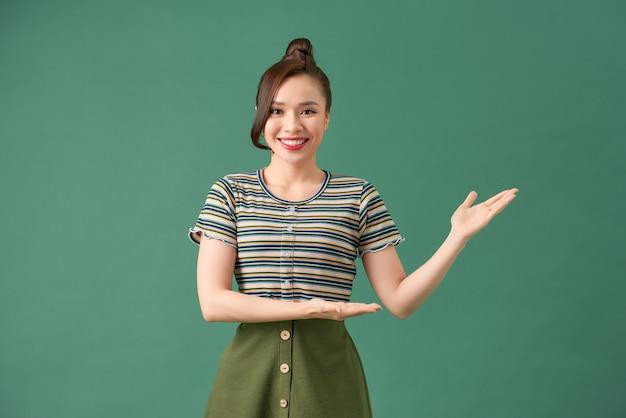 Młoda kobieta pokazuje coś z odizolowaną zielenią