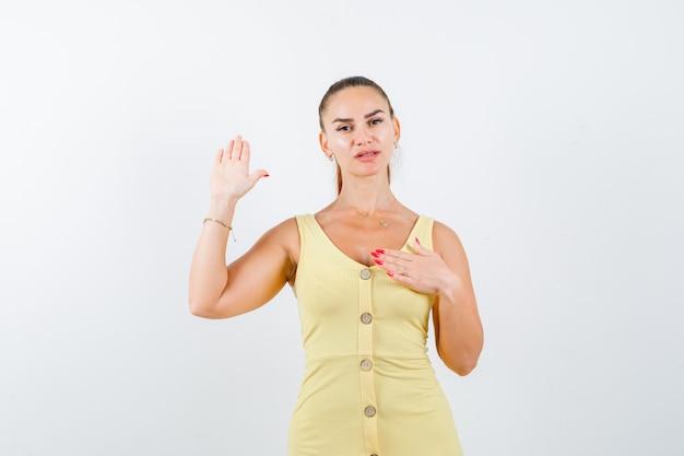 Młoda kobieta pokazuje dłoń, trzyma rękę na piersi w żółtej sukience i wygląda pewnie, widok z przodu.