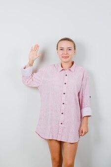 Młoda kobieta pokazuje dłoń w różowej koszuli i wygląda wesoło