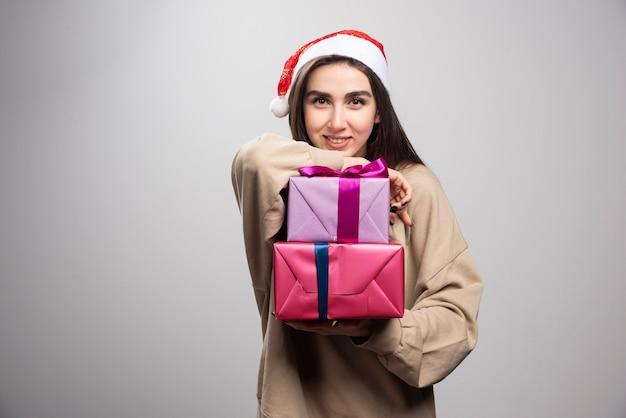 Młoda kobieta pokazuje dwa prezenty świąteczne.