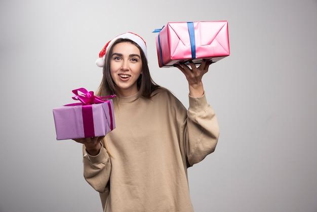 Młoda kobieta pokazuje dwa pudełka prezentów świątecznych.