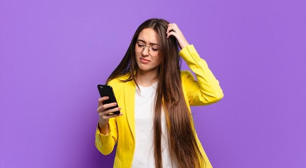 Młoda kobieta pokazuje ekran jej komórki