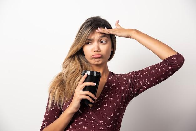 Młoda kobieta pokazuje filiżankę napoju na białej ścianie.
