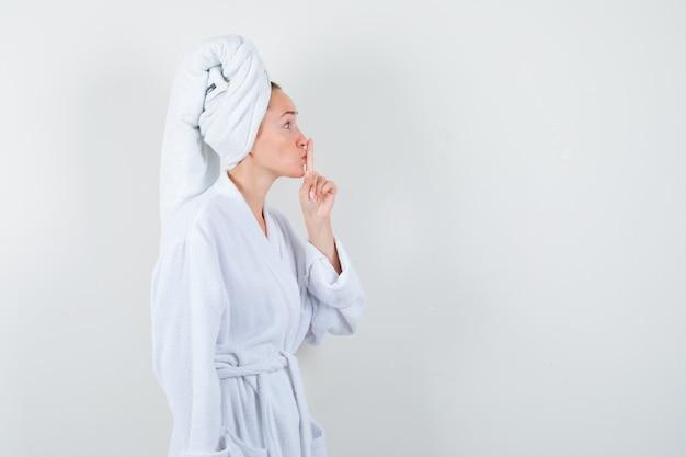 Młoda kobieta pokazuje gest ciszy w biały szlafrok, ręcznik i patrząc ostrożnie. przedni widok.