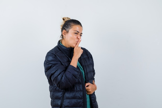 Młoda kobieta pokazuje gest ciszy w puchowej kurtce i wygląda rozsądnie, widok z przodu.