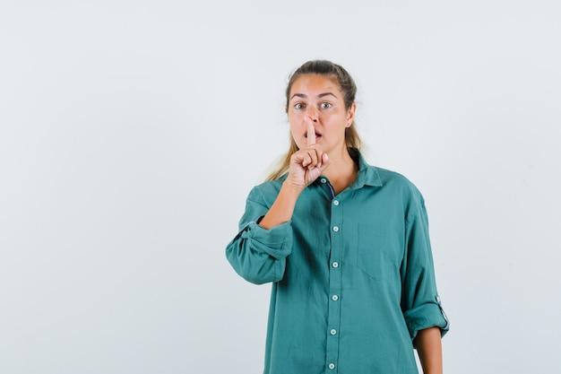 Młoda kobieta pokazuje gest ciszy w zielonej bluzce i wygląda poważnie