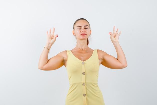 Młoda kobieta pokazuje gest jogi z zamkniętymi oczami w żółtej sukience i wygląda zrelaksowany. przedni widok.