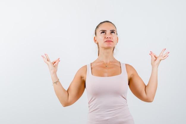 Młoda kobieta pokazuje gest medytacji w podkoszulku i wygląda spokojnie. przedni widok.