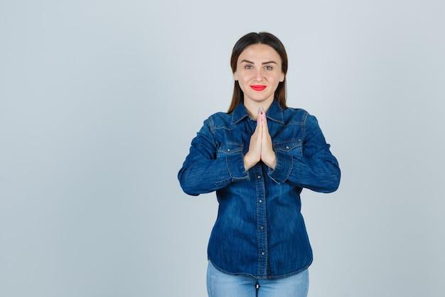 Młoda kobieta pokazuje gest namaste w dżinsowej koszuli i dżinsach i szuka spokoju