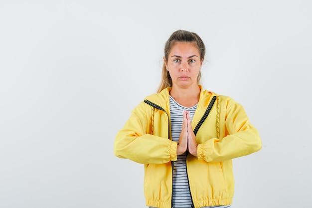 Młoda kobieta pokazuje gest namaste w koszulce, kurtce i patrząc spokojny, przedni widok.