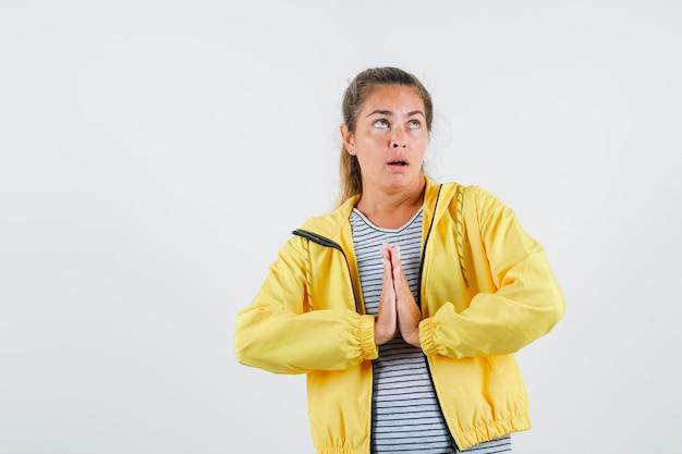 Młoda kobieta pokazuje gest namaste w kurtce, t-shirt i patrząc z nadzieją, widok z przodu.