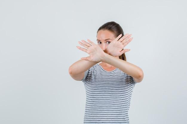Młoda kobieta pokazuje gest odmowy w koszulce i patrząc poważny, przedni widok.