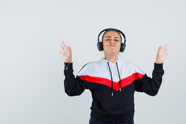 Młoda kobieta pokazuje gest ok podczas słuchania muzyki w kolorowej bluzie, słuchawkach i patrząc skupiony. przedni widok.