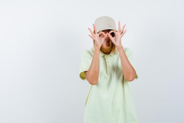 Młoda kobieta pokazuje gest okulary w t-shirt, czapka i patrząc zabawny, widok z przodu.