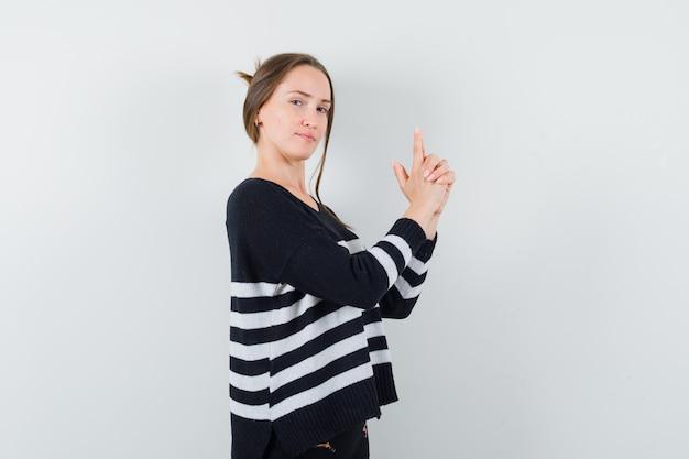 Młoda kobieta pokazuje gest pistoletu w dzianinie w paski i czarne spodnie i wygląda pewnie