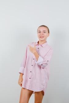 Młoda kobieta pokazuje gest pistoletu w różowej koszuli i wygląda wesoło
